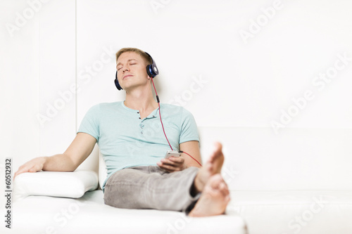 Relaxed man listening to music with earphones and eyes closed.