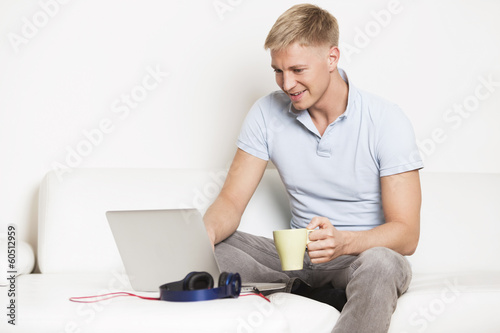 Man enjoying a cup of coffee while working on computer.