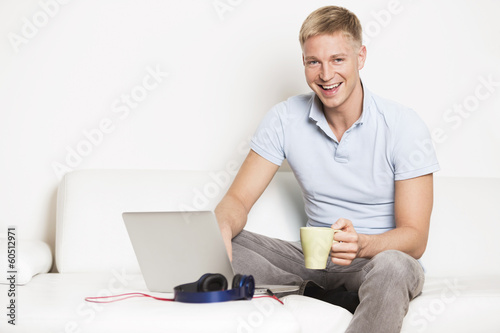 Joyous man sitting on couch with laptop and drinking coffee.