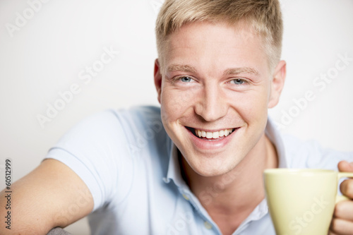Joyful laughing young man enjoying a cup of coffee.