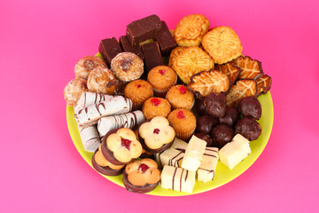Sweet cookies on plate on pink background