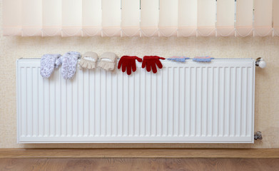 Knitted gloves drying on heating radiator