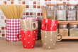 Cups in kitchen on table on mosaic tiles background