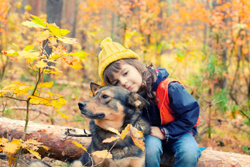 Serious little girl with her dog in the forest