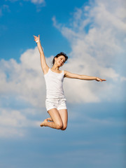 Girl in white hopping with arm raised on background of sky