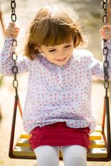 Pretty girl in park swinging