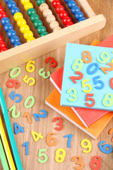 Colorful numbers, abacus, books and markers on wooden