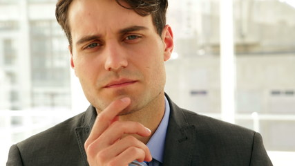 Businessman looking thoughtfully at camera