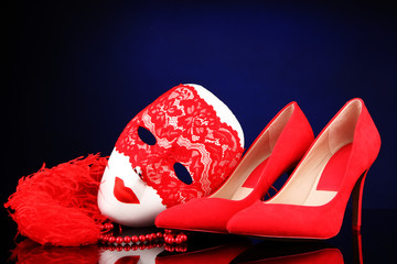 Beautiful red female shoes and carnival mask, on blue