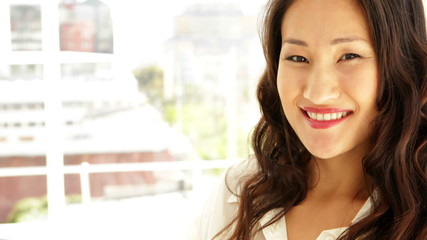 Asian businesswoman smiling at camera with arms crossed