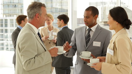 Business people chatting at a conference having coffee