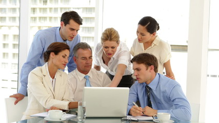 Happy business team working in front of laptop