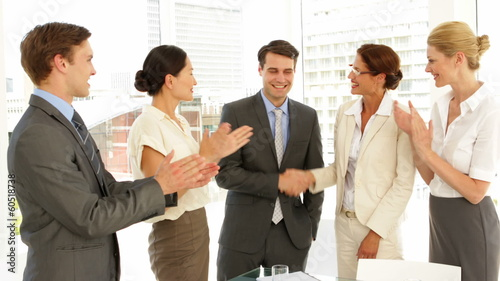 Business people shaking hands at interview while others clap