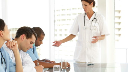 Doctor speaking to her staff during meeting