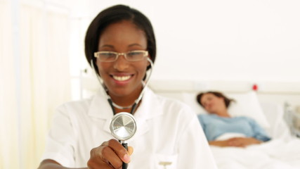 Smiling nurse in the ward holding her stethoscope