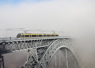Metro Train on the Bridge Built by Eiffel in Porto, foggy mornin