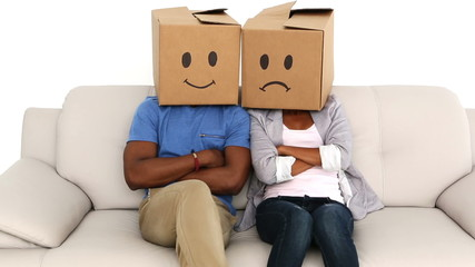 Team sitting on sofa with emoticon boxes on their heads