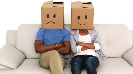 Partners sitting on sofa with emoticon boxes on their heads
