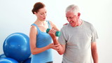 Older man lifting hand weights with the help of his trainer