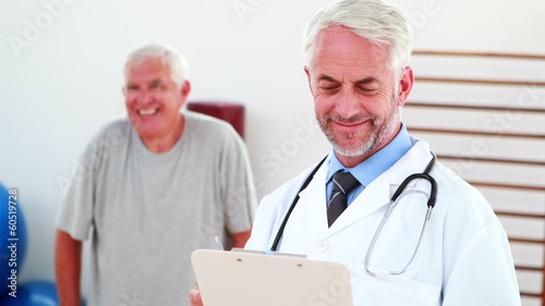 Smiling doctor reading from clipboard
