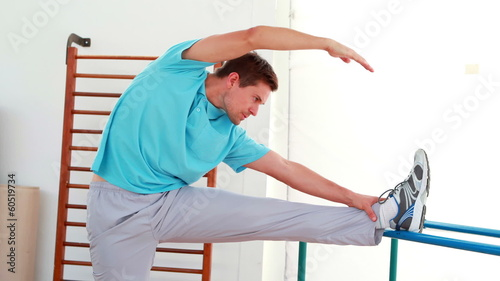 Flexible man stretching his leg