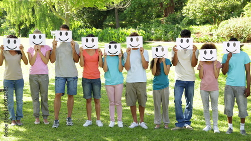 Group of young friends holding smiley faces over their faces