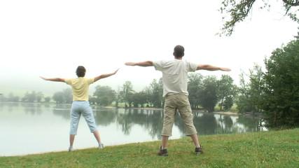 Paar macht Gymnastik  am See mit Nebel