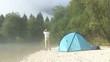 Wanderer mit Fernglas neben seinem Zelt an einem Gebirgsfluss.