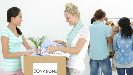 Team of people going through donation box of clothes
