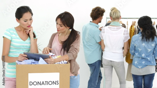 Team of smiling workers using tablet beside donation box