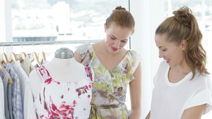 Two friends admiring a dress on a mannequin