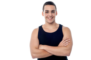 Smiling young fitness guy, arms crossed