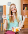 Pretty long-haired woman eating  fruit salad with yoghurt