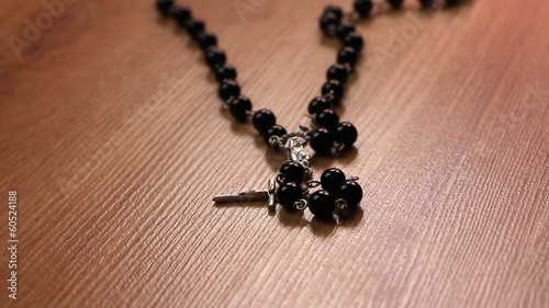 Black rosary falling down the floor