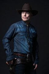 Modern fashion cowboy. Wearing brown hat and blue jeans shirt. P