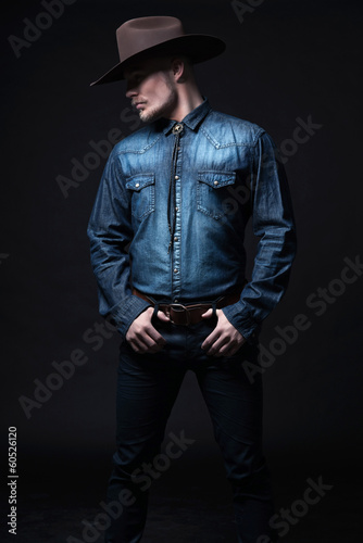 Modern fashion cowboy. Wearing brown hat and blue jeans shirt. B