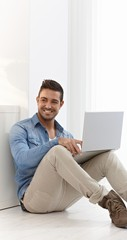 Happy young man browsing internet at home