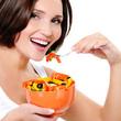 Young woman eats vegetable