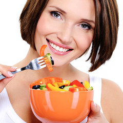 Young woman eats vegetable