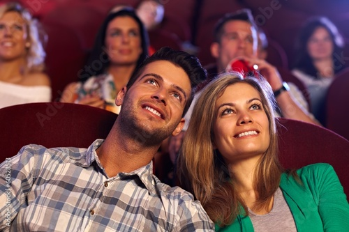 Happy couple watching movie in cinema