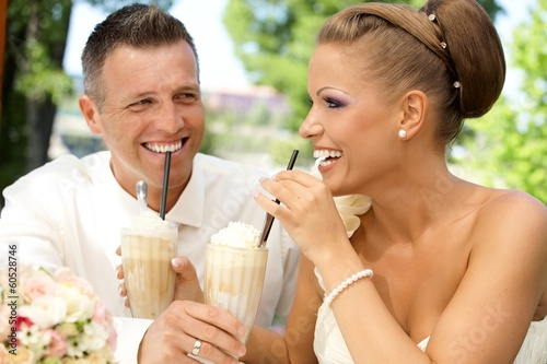 Happy couple drinking ice coffee on wedding-day