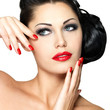 Beautiful woman with red nails and fashion makeup