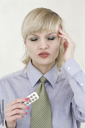 Young beautiful business woman with migraine and pills