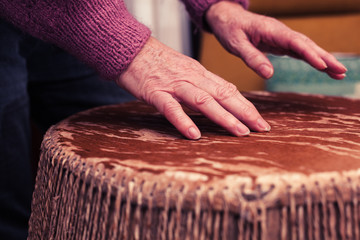 Old woman playing bongo drums