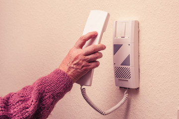 Old woman answering intercom