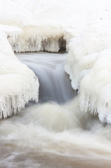 Flowing river and icicles in winter