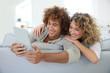 Cheerful couple having fun using tablet in sofa