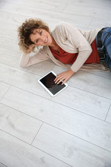 Woman laying on the floor with digital tablet