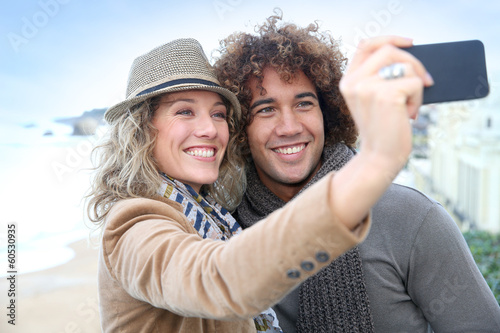 Cheerful couple taking picture with smartphone