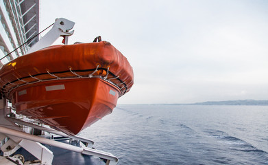 Orange Lifeboat Hanging Over Grey Water